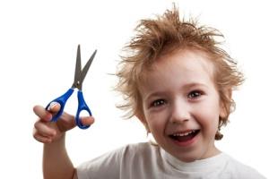 Dishevelled hair smile child hand holding scissors